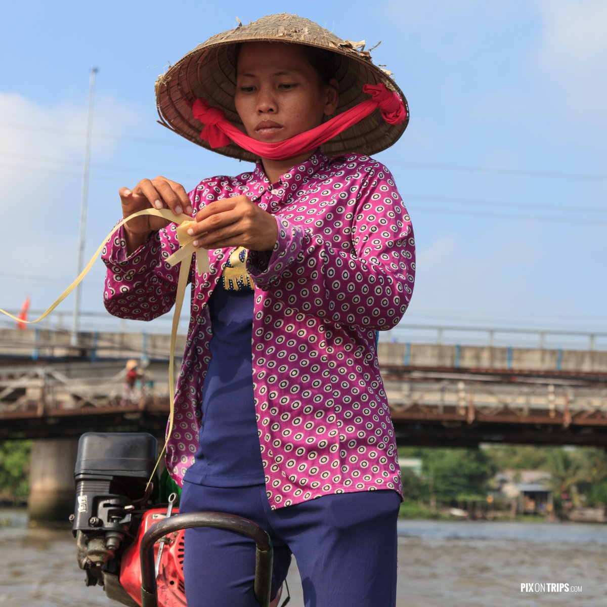 Boat driver making reed flower on Mekong River, Vietnam - Pix on Trips