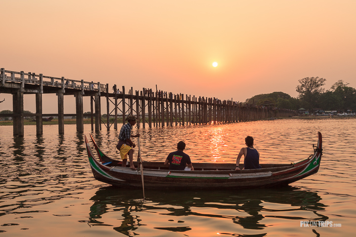 Tourists watch sunset from boat beside U Bien Bridge, Mandalay, Myanmar