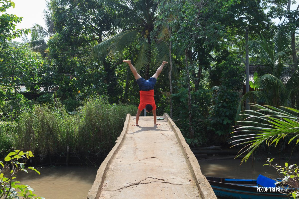 Man doing handstand on bridge in Mekong River Delta, Vietnam - Pix on Trips