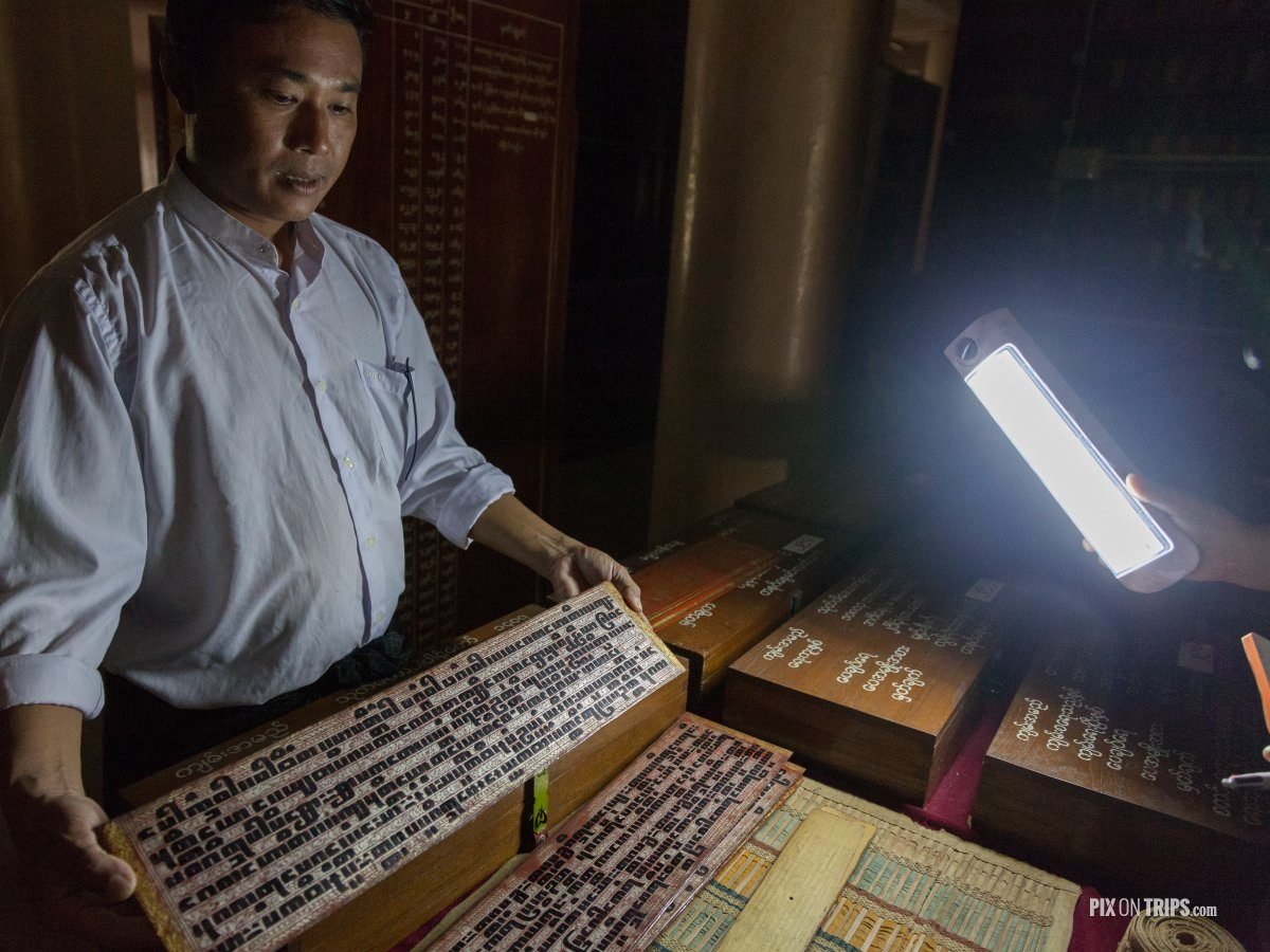 Guide at Shwe In Bin Kyaung monastery in Mandalay, Myanmar showing 500 year-old Buddist writings