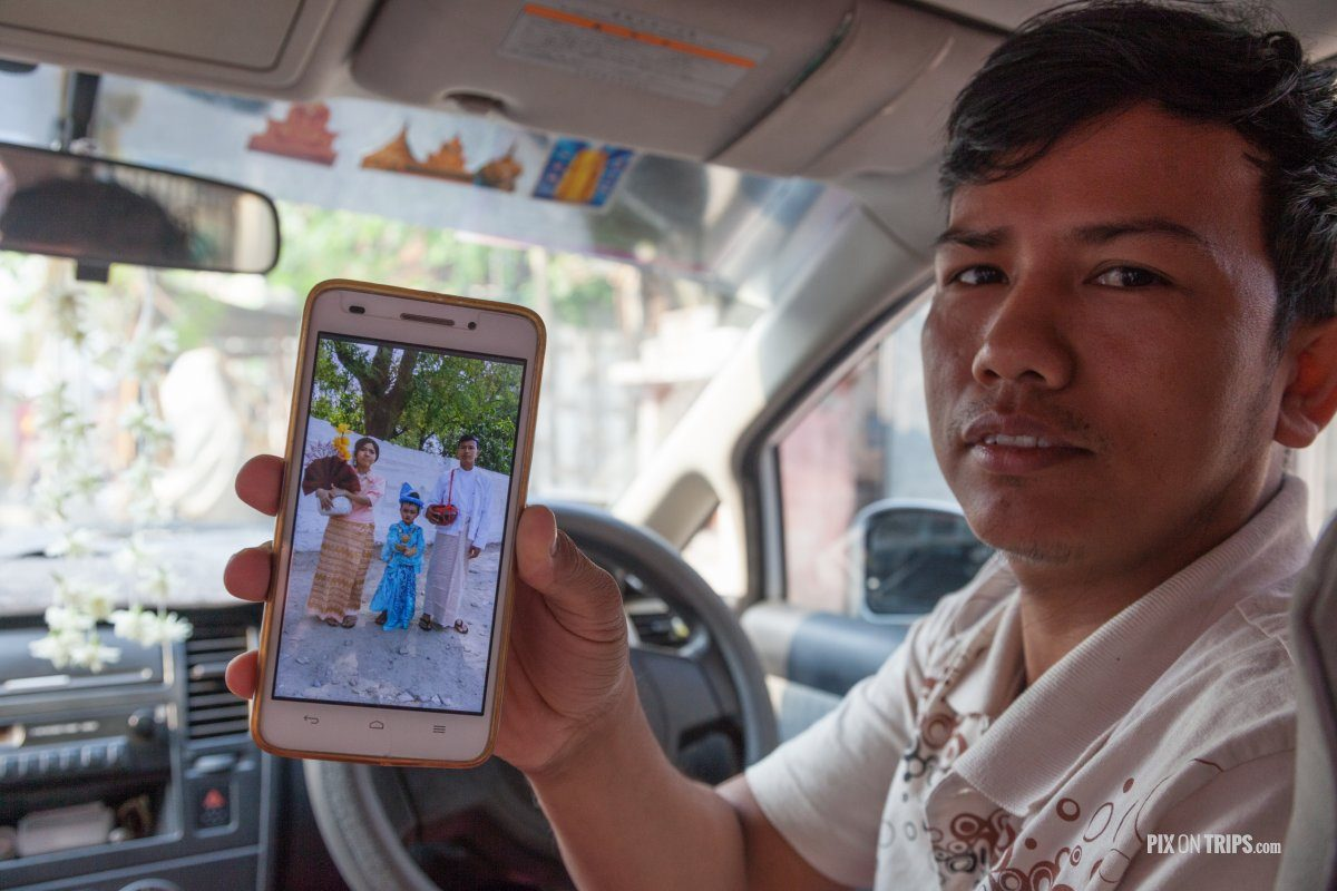 Taxi driver showing photo of family, Mandalay, Myanmar