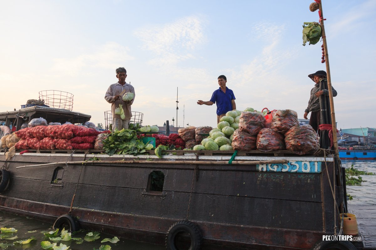 Vendors paring vegetables at Cai Rang floating market, Vietnam - Pix on Trips