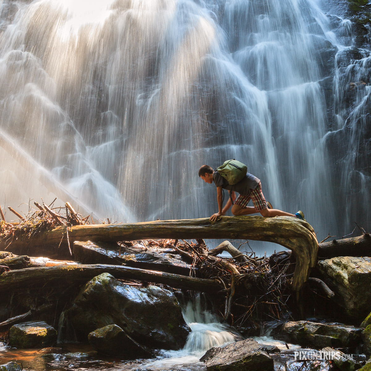 A teenager boy attempting to crawl cross a tree log in front of Crabtree Falls - Pix on Trips