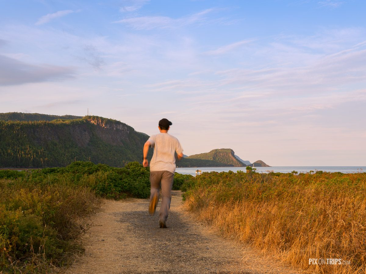 Man running along a trail leading to Bay Ha Ha in Parc National du Bic Quebec
