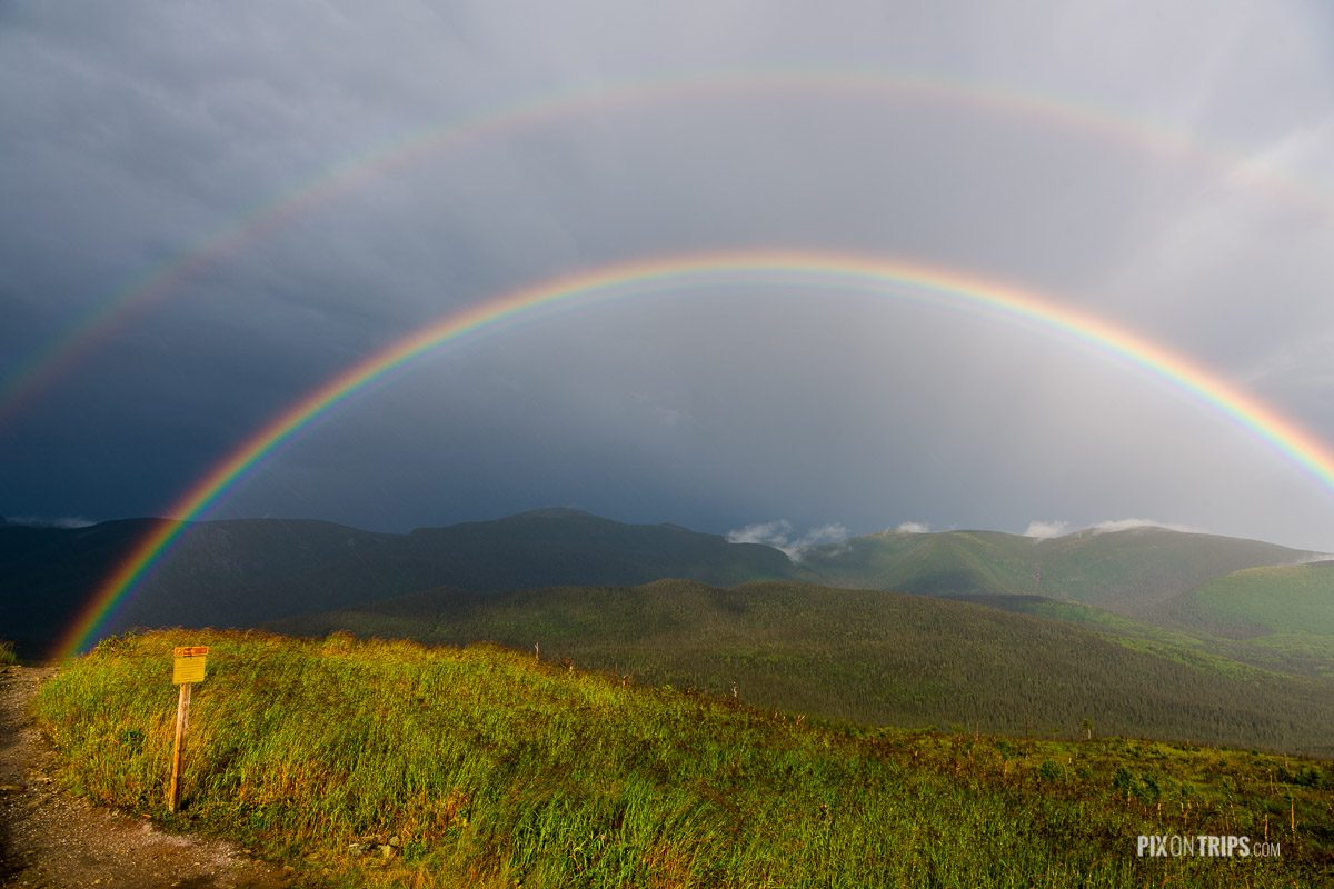 Rainbow at the summit of Mont Ernest Laforce in Parc National de la Gaspesie with mountain ranges in the background