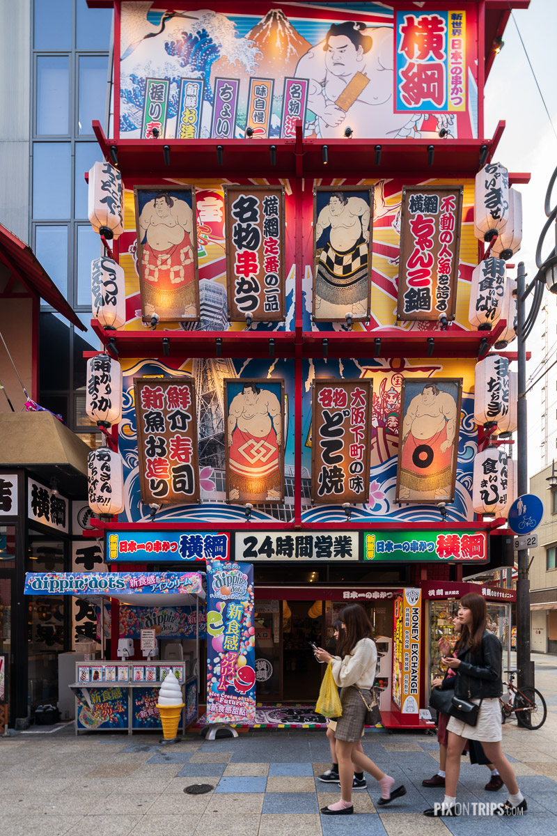 Japanese girls walk by a building full of signs in the Shinsekai District of Osaka, Japan - Pix on Trips