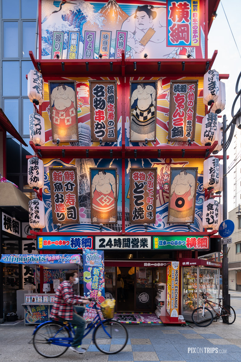 Woman riding bicycle passes a building full of signs, Osaka, Japan - Pix on Trips